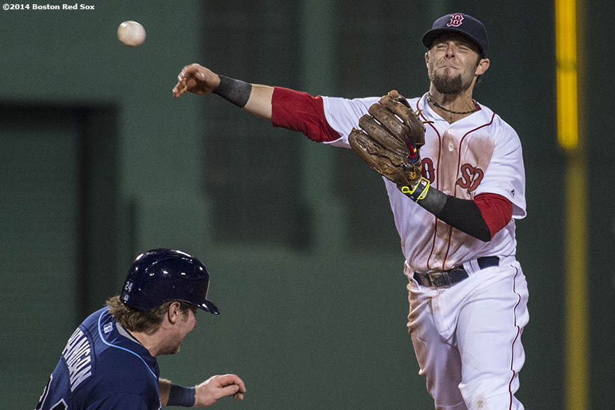"""Boston Red Sox second baseman Dustin Pedroia turns a double play during the fourth inning of the second game of a day-night double header against the Tampa Bay Rays Thursday, May 2, 2014 at Fenway Park in Boston, Massachusetts."""