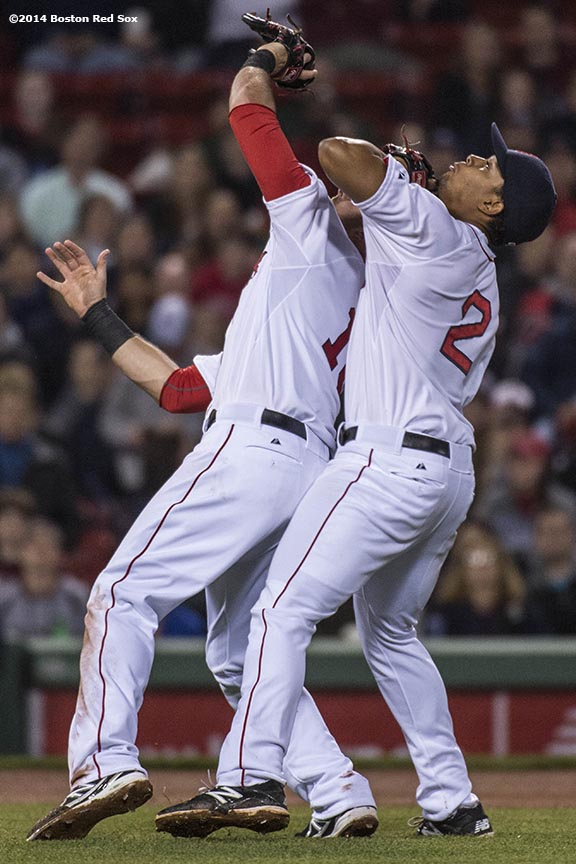 """Boston Red Sox third baseman Will Middlebrooks and shortstop Xander Bogaerts collide while attempting to catch a foul ball during the sixth inning of the second game of a day-night double header against the Tampa Bay Rays Thursday, May 2, 2014 at Fenway Park in Boston, Massachusetts."""