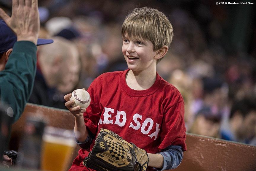 """A young fan catches a foul ball during the second game of a day-night double header between the Boston Red Sox and the Tampa Bay Rays Thursday, May 2, 2014 at Fenway Park in Boston, Massachusetts."""
