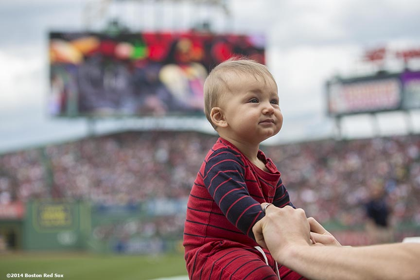 """A baby sits on a ledge during a game between the Boston Red Sox and the Oakland Athletics Saturday, May 4, 2014 at Fenway Park in Boston, Massachusetts."""