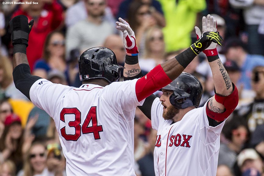 """Boston Red Sox left fielder Jonny Gomes high fives designated hitter David Ortiz after hitting a grand slam home run during the first inning of a game against the Oakland Athletics Saturday, May 4, 2014 at Fenway Park in Boston, Massachusetts."""