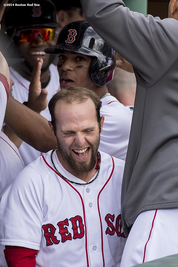 """Boston Red Sox second baseman Dustin Pedroia laughs after scoring on a grand slam home run by Jonny Gomes during the first inning of a game against the Oakland Athletics Saturday, May 4, 2014 at Fenway Park in Boston, Massachusetts."""