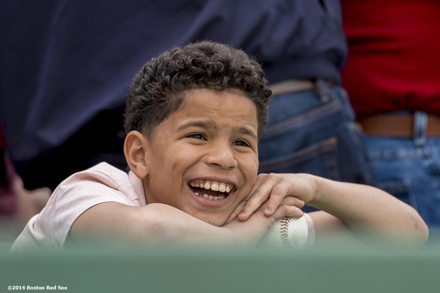 """A young fan cheers during a game between the Boston Red Sox and the Oakland Athletics Saturday, May 4, 2014 at Fenway Park in Boston, Massachusetts."""