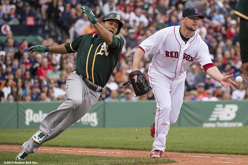 """Boston Red Sox pitcher Jon Lester tosses to first base after missing a tag on outfielder Coco Crisp during the sixth inning of a game against the Oakland Athletics Saturday, May 4, 2014 at Fenway Park in Boston, Massachusetts."""