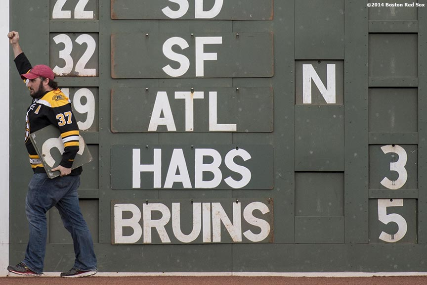 """A Green Monster scoreboard worker cheers after posting the final score of the Boston Bruins NHL playoff game during a game between the Boston Red Sox and the the Oakland Athletics Saturday, May 4, 2014 at Fenway Park in Boston, Massachusetts."""