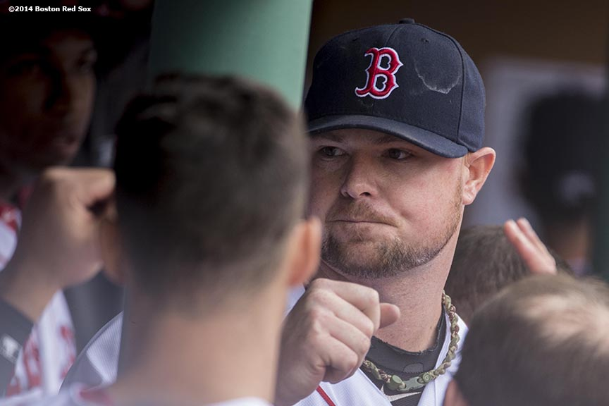 """Boston Red Sox pitcher Jon Lester high fives teammates after striking out 15 batters during the eighth inning of a game against the Oakland Athletics Saturday, May 4, 2014 at Fenway Park in Boston, Massachusetts."""