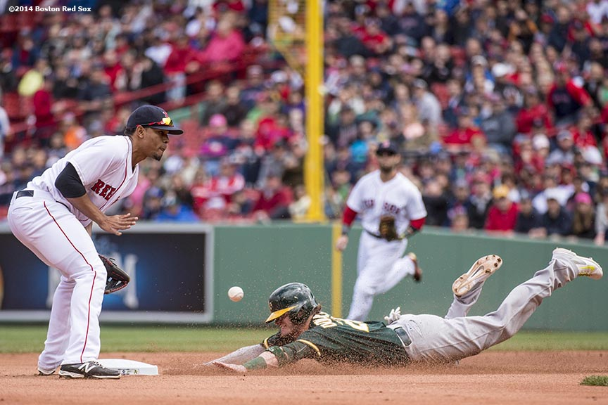 """Boston Red Sox shortstop Xander Bogaerts fields a throw from catcher A.J. Pierzynski to tag third baseman Josh Donaldson during the third inning of a game against the Oakland Athletics Sunday, May 5, 2014 at Fenway Park in Boston, Massachusetts."""