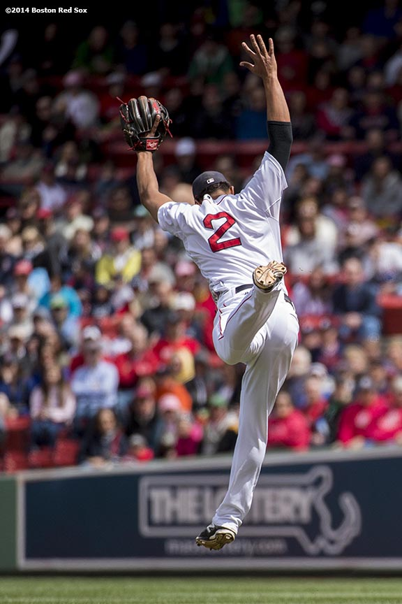 """Boston Red Sox shortstop Xander Bogaerts leaps for a line drive during the first inning of a game against the Oakland Athletics Sunday, May 5, 2014 at Fenway Park in Boston, Massachusetts."""