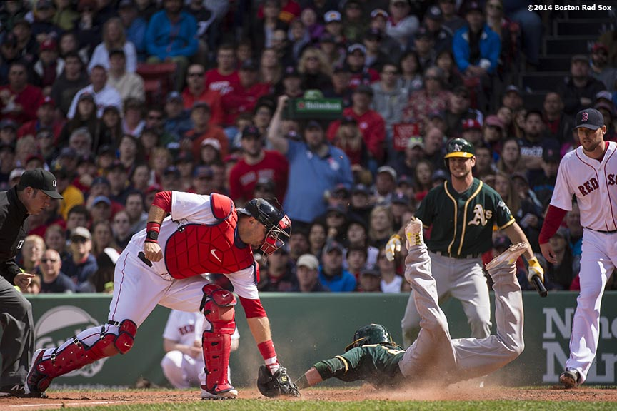 """Boston Red Sox catcher A.J. Pierzynski applies a tag on third baseman Josh Donaldson during the sixth inning of a game against the Oakland Athletics Sunday, May 5, 2014 at Fenway Park in Boston, Massachusetts."""
