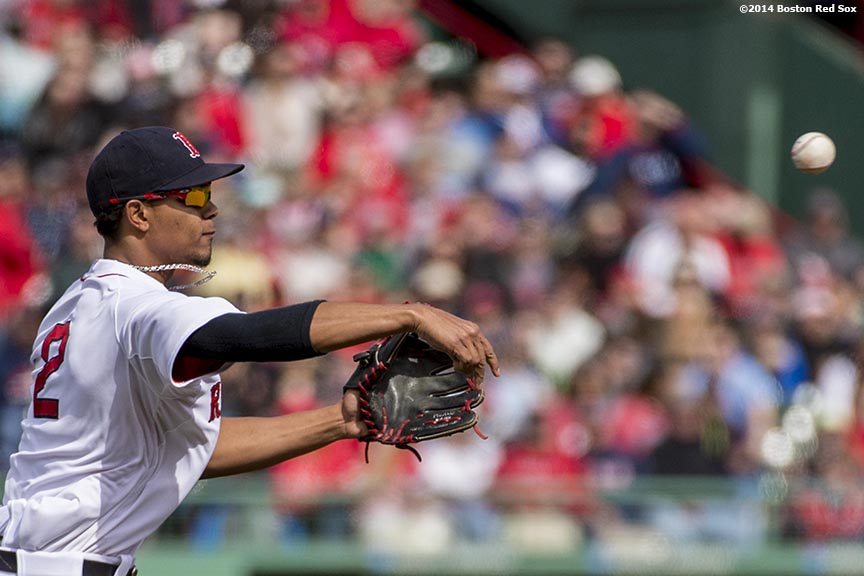 """Boston Red Sox shortstop Xander Bogaerts throws to first base during the sixth inning of a game against the Oakland Athletics Sunday, May 5, 2014 at Fenway Park in Boston, Massachusetts."""