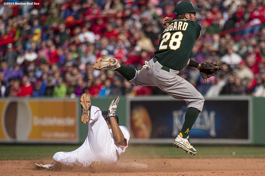 """Boston Red Sox shortstop Xander Bogaerts slides into second base as second baseman Eric Sogard turns a double play during the tenth inning of a game against the Oakland Athletics Sunday, May 5, 2014 at Fenway Park in Boston, Massachusetts."""