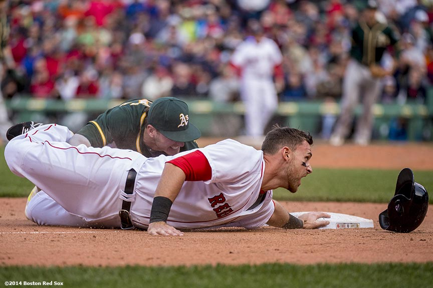 """Boston Red Sox third baseman Will Middlebrooks is tagged out as he slides into third base by third baseman Josh Donaldson during the tenth inning of a game against the Oakland Athletics Sunday, May 5, 2014 at Fenway Park in Boston, Massachusetts."""