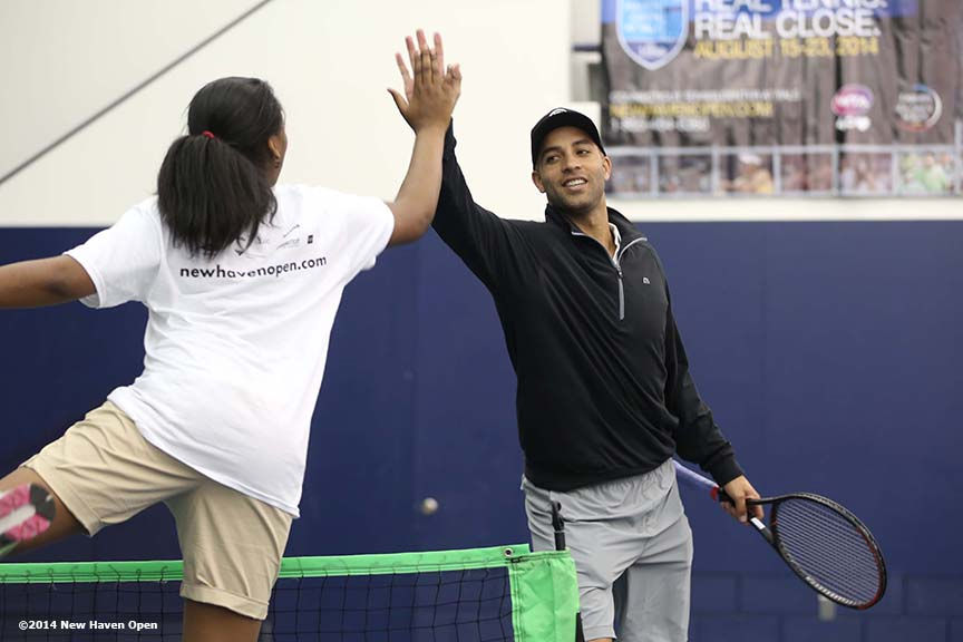 """Former professional tennis player James Blake high fives a participant during a free tennis lesson and clinic Thursday, May 15, 2014 in advance of the 2014 New Haven Open at the Yale University Tennis Center in New Haven, Connecticut. """