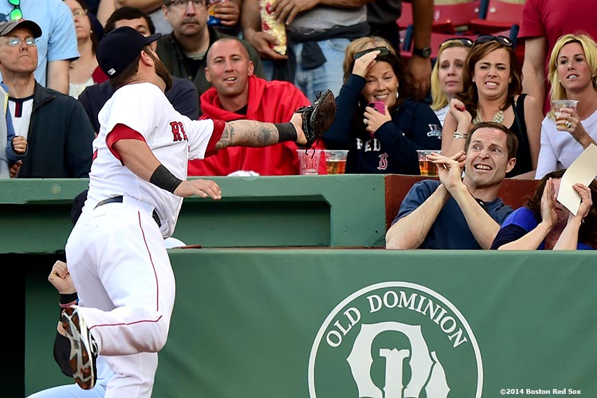 """Boston Red Sox  first baseman Mike Napoli reaches into the stands to catch a foul ball during the first inning of a game against the Detroit Tigers at Fenway Park in Boston, Massachusetts Saturday, May 17, 2014."""