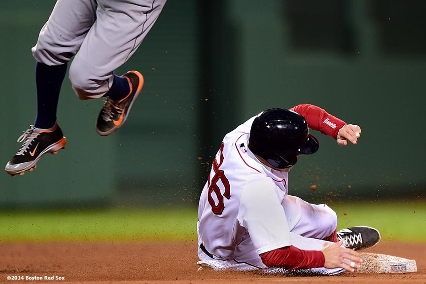 """Boston Red Sox third baseman Brock Holt  steals second base as shortstop Andrew Romine jumps for a wild throw during the sixth inning of a game against the Detroit Tigers at Fenway Park in Boston, Massachusetts Sunday, May 18, 2014."""