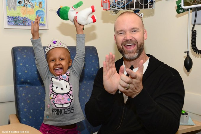 """Boston Red Sox catcher David Ross shares a laugh with Jimmy Fund patient Eliana Montas, 3, of Clinton, Massachusetts during a visit to the Jimmy Fund at the Dana-Farber Cancer Institute in Boston, Massachusetts Wednesday, May 21, 2014."""