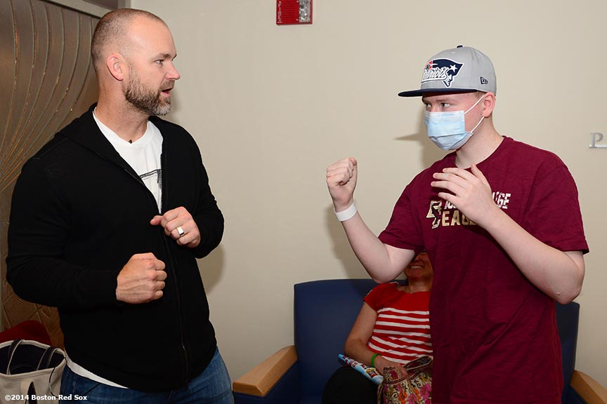 """Boston Red Sox catcher David Ross greets a patient during a visit to the Jimmy Fund at the Dana Farber Cancer Institute in Boston, Massachusetts Wednesday, May 21, 2014."""