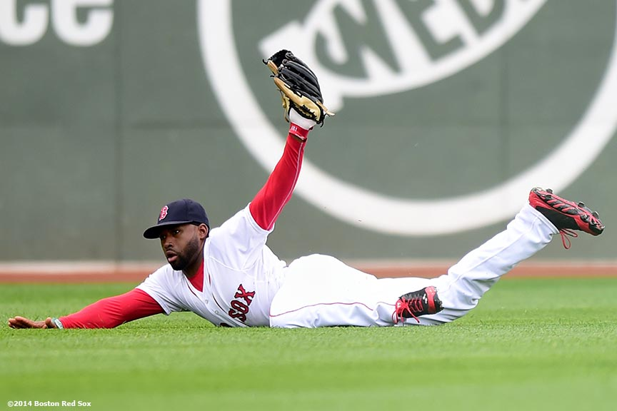 """Boston Red Sox center fielder Jackie Bradley Jr. reveals the ball after making a diving catch during the second inning of a game against the Toronto Blue Jays Thursday, May 22, 2014 at Fenway Park in Boston, Massachusetts."""