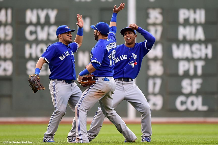 """Toronto Blue Jays outfielders Jose Bautista, Anthony Gose, and Melky Cabrera celebrate after defeating the Boston Red Sox Thursday, May 22, 2014 at Fenway Park in Boston, Massachusetts."""