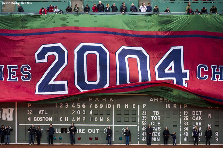 """A banner is unfurled over the Green Monster during a pre-game ceremony honoring the ten year anniversary and team reunion of the 2004 World Series champion Boston Red Sox at Fenway Park in Boston, Massachusetts Wednesday, May 28, 2014."""
