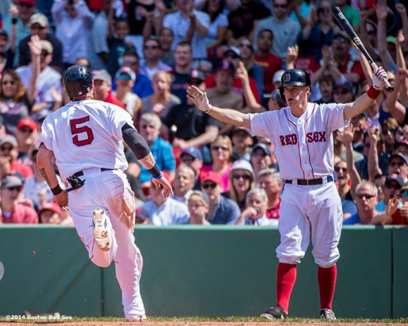 """""""Boston Red Sox first baseman Brock Holt gestures as left fielder Jonny Gomes scores on a sacrifice fly by second baseman Jonathan Herrera during the fourth inning of a game against the Tampa Bay Rays at Fenway Park in Boston, Massachusetts Sunday, June 1, 2014."""""""