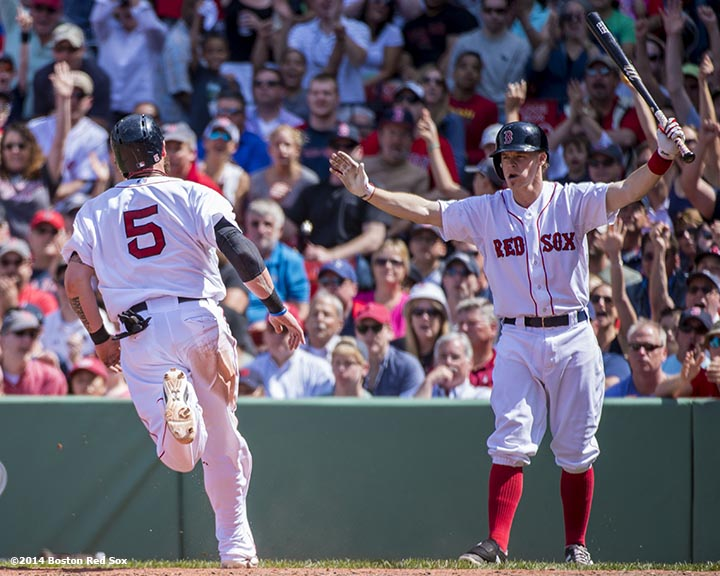 """Boston Red Sox first baseman Brock Holt gestures as left fielder Jonny Gomes scores on a sacrifice fly by second baseman Jonathan Herrera during the fourth inning of a game against the Tampa Bay Rays at Fenway Park in Boston, Massachusetts Sunday, June 1, 2014."""