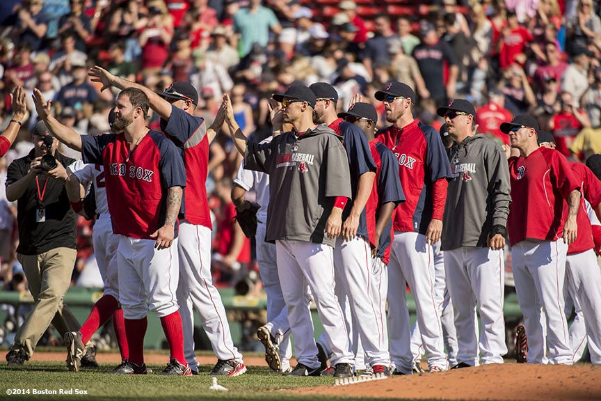 """Boston Red Sox teammates line up to high five each other after defeating the Tampa Bay Rays at Fenway Park in Boston, Massachusetts Sunday, June 1, 2014."""