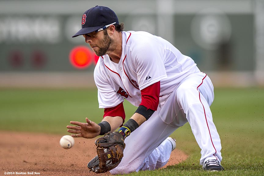 """Boston Red Sox second baseman Dustin Pedroia fields a ground ball during the sixth inning of a game against the Cleveland Indians Saturday, June 14, 2014 at Fenway Park in Boston, Massachusetts."""