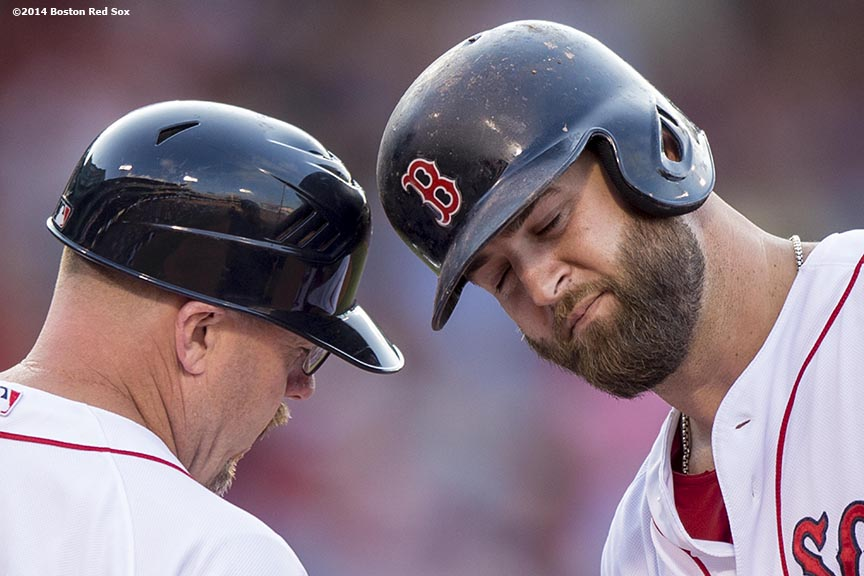 """Boston Red Sox first baseman Mike Napoli bumps helmets with first base coach Arnie Beyeler after hitting a single during the eighth inning of a game against the Cleveland Indians Saturday, June 14, 2014 at Fenway Park in Boston, Massachusetts."""