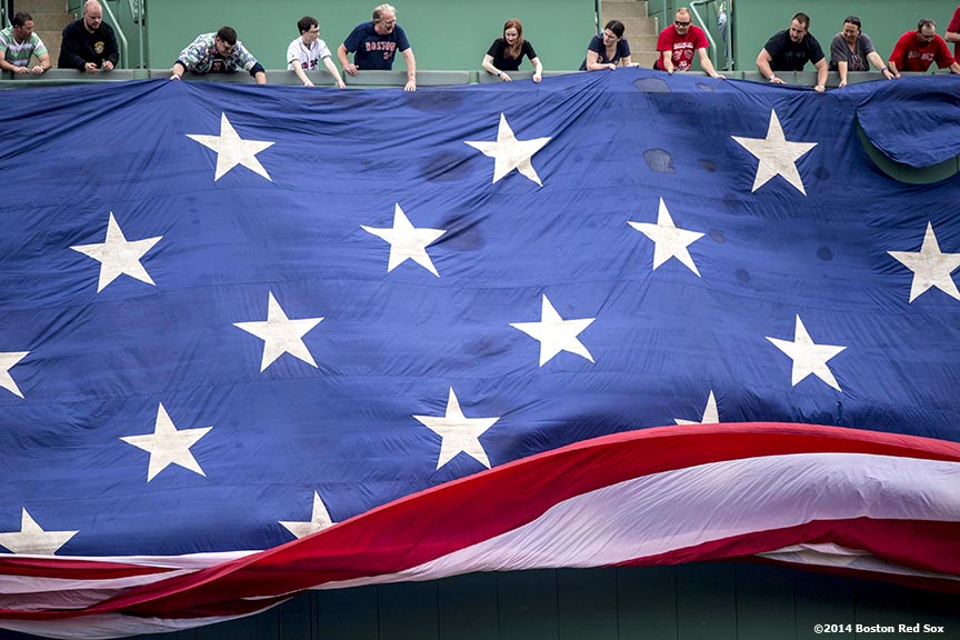 """Fans unfurl an American flag over the Green Monster during a pre-game ceremony before a game between the Boston Red Sox and the Cleveland Indians Saturday, June 14, 2014 at Fenway Park in Boston, Massachusetts."""