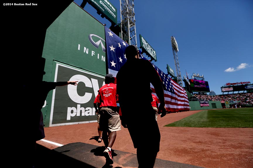 """Grounds crew members enter the field during a ceremony before a game between the Boston Red Sox and the Cleveland Indians at Fenway Park in Boston, Massachusetts Sunday, June 15, 2014."""