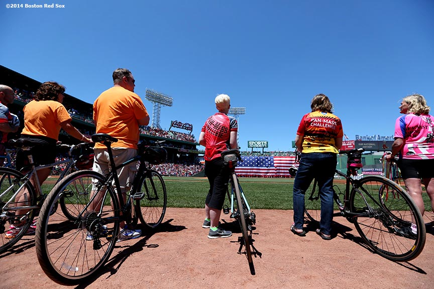 """Members of the Pan-Mass Challenge ride bikes around the warning track during a ceremony before a game between the Boston Red Sox and the Cleveland Indians at Fenway Park in Boston, Massachusetts Sunday, June 15, 2014."""