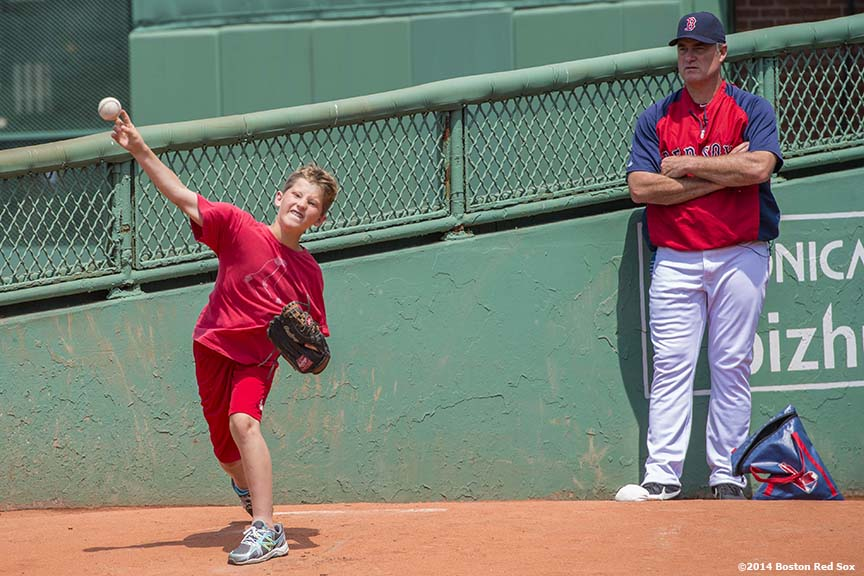 """Boston Red Sox manager John Farrell instructs two boys during a private pitching lesson, won as an auction item, at Fenway Park in Boston, Massachusetts Tuesday, June 17, 2014."""