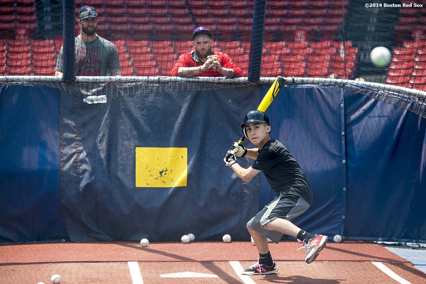"""Boston Red Sox left fielder Jonny Gomes and first baseman Mike Napoli watch as a guest takes batting practice during a Wise company corporate sponsorship appreciation event on the field at Fenway Park in Boston, Massachusetts Tuesday, June 17, 2014."""