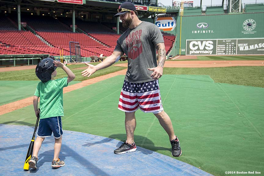 """A young guest high fives first baseman Mike Napoli after taking batting practice during a Wise company corporate sponsorship appreciation event on the field at Fenway Park in Boston, Massachusetts Tuesday, June 17, 2014."""