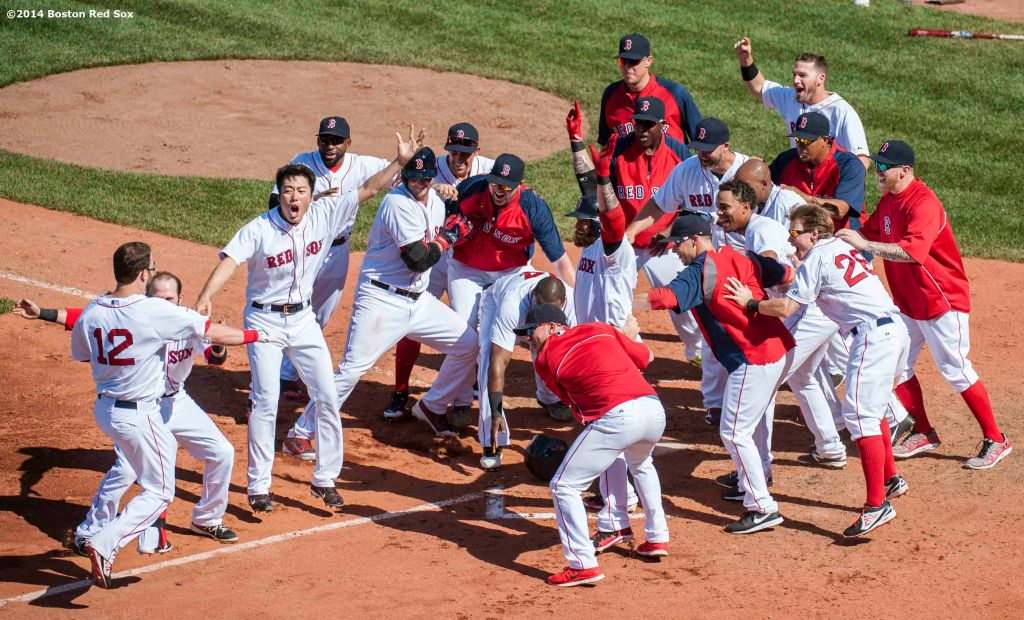 """Boston Red Sox players celebrate as they mob first baseman Mike Napoli after hitting a walk-off solo home run to defeat the Minnesota Twins 2-1 in the bottom of the tenth inning at Fenway Park in Boston, Massachusetts Tuesday, June 18, 2014."""