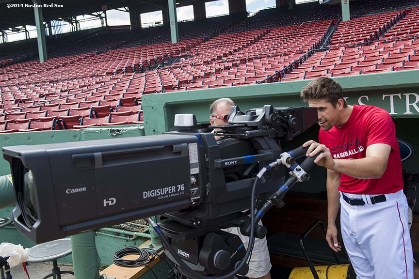 """Boston Red Sox third baseman Garin Cecchini tests out a camera alongside operator Bob Tomaselli in the dugout before a game against the Minnesota Twins at Fenway Park in Boston, Massachusetts Tuesday, June 18, 2014."""