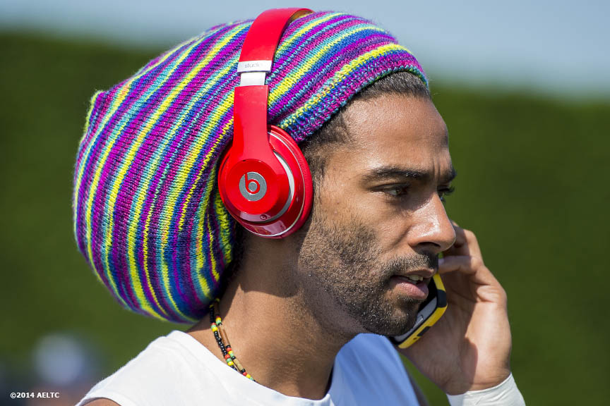 """Dustin Brown talks on the phone before a practice session at the All England Lawn and Tennis Club in London, England Saturday, June 21, 2014 during the 2014 Championships Wimbledon."""