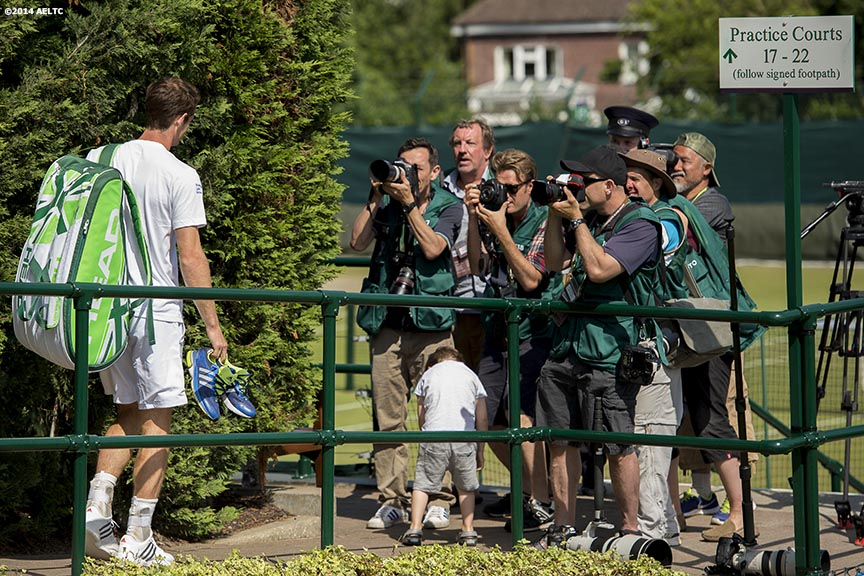 """Andy Murray walks toward a corral of photographers at the Aorangi practice courts at the All England Lawn and Tennis Club in London, England Sunday, June 22, 2014 during the 2014 Championships Wimbledon."""
