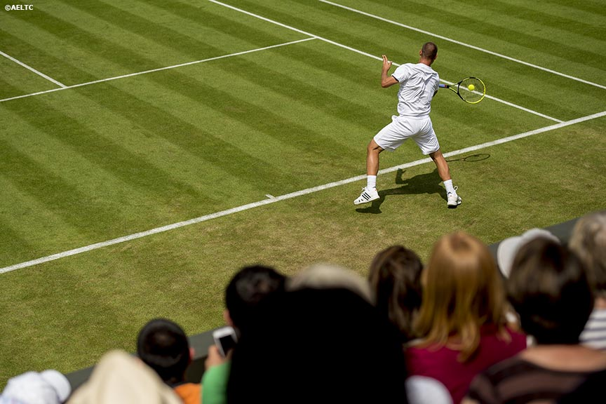 """Fans watch as Mikhail Youzhny hits a forehand against James Ward at the All England Lawn and Tennis Club in London, England Monday, June 23, 2014 during the 2014 Championships Wimbledon."""