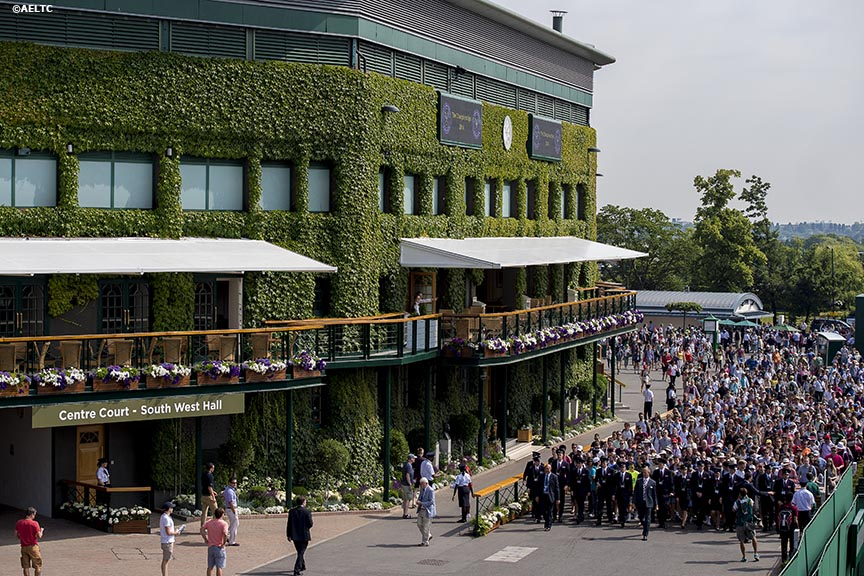 """Fans are escorted into the grounds of the All England Lawn and Tennis Club in London, England Tuesday, June 24, 2014 during the 2014 Championships Wimbledon."""