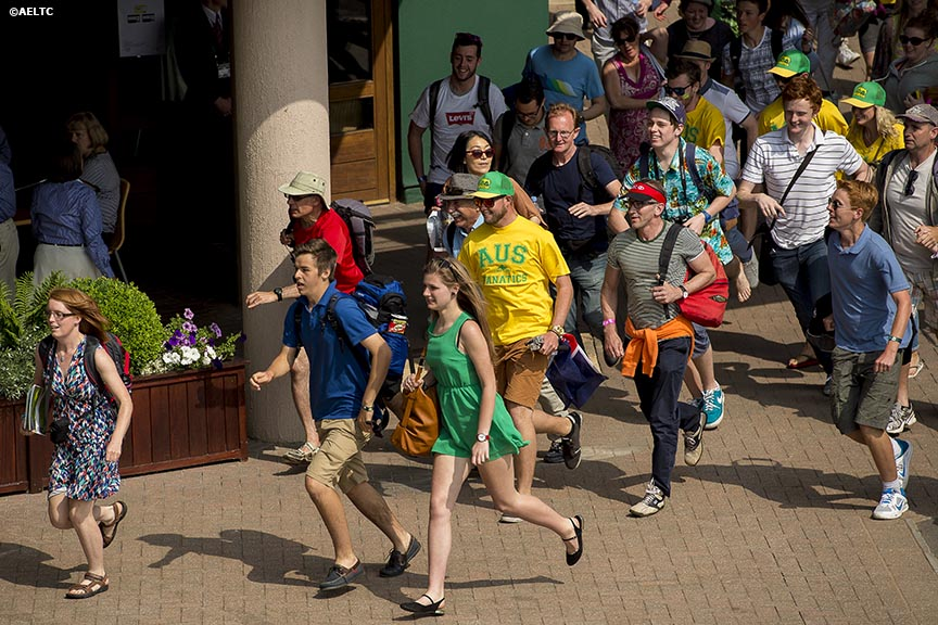 """Fans run toward the courts at the All England Lawn and Tennis Club in London, England Tuesday, June 24, 2014 during the 2014 Championships Wimbledon."""