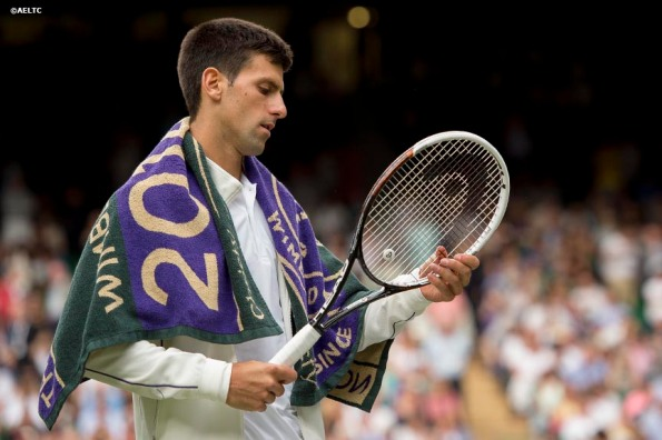 """""""Novak Djokovic inspects his racquet during a match against Radek Stepanek on Centre Court at the All England Lawn and Tennis Club in London, England Tuesday, June 24, 2014 during the 2014 Championships Wimbledon."""""""