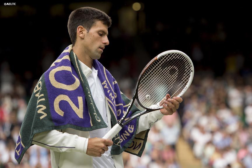 """Novak Djokovic inspects his racquet during a match against Radek Stepanek on Centre Court at the All England Lawn and Tennis Club in London, England Tuesday, June 24, 2014 during the 2014 Championships Wimbledon."""