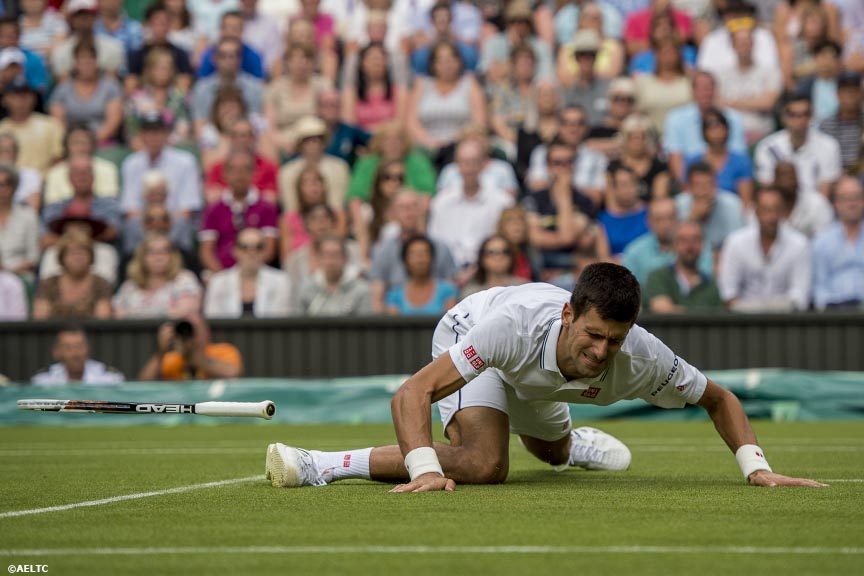 """Novak Djokovic loses his racquet as he falls during a match against Radek Stepanek on Centre Court at the All England Lawn and Tennis Club in London, England Tuesday, June 24, 2014 during the 2014 Championships Wimbledon."""