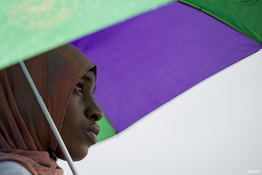 """A fan stands under an umbrella as she watches a match on Henman Hill at the All England Lawn and Tennis Club in London, England Saturday, June 28, 2014 during the 2014 Championships Wimbledon."""