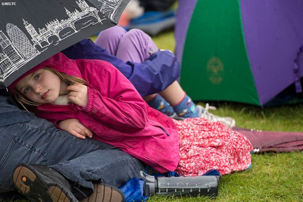 """""""A young fan sits under an umbrella during a rain delay at the All England Lawn and Tennis Club in London, England Saturday, June 28, 2014 during the 2014 Championships Wimbledon."""""""