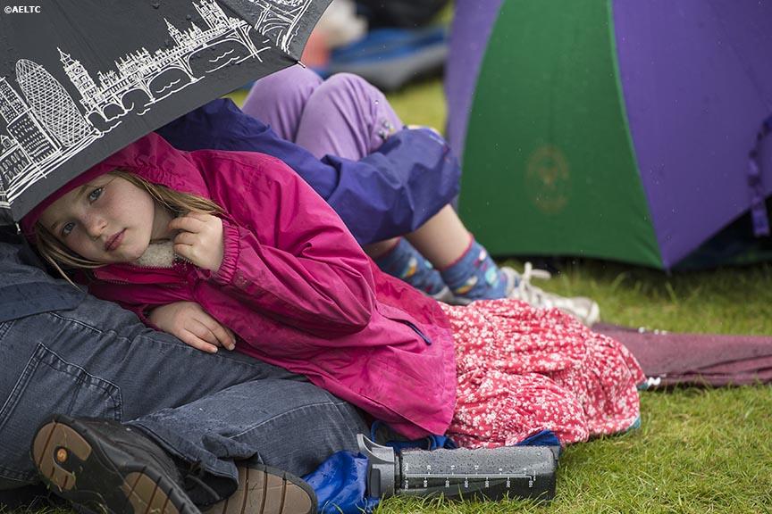"""A young fan sits under an umbrella during a rain delay at the All England Lawn and Tennis Club in London, England Saturday, June 28, 2014 during the 2014 Championships Wimbledon."""