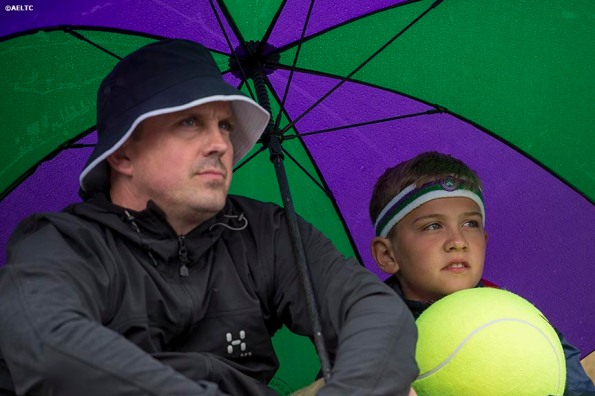 """""""Fans sit under an umbrella as they watch a match on Henman Hill at the All England Lawn and Tennis Club in London, England Saturday, June 28, 2014 during the 2014 Championships Wimbledon."""""""