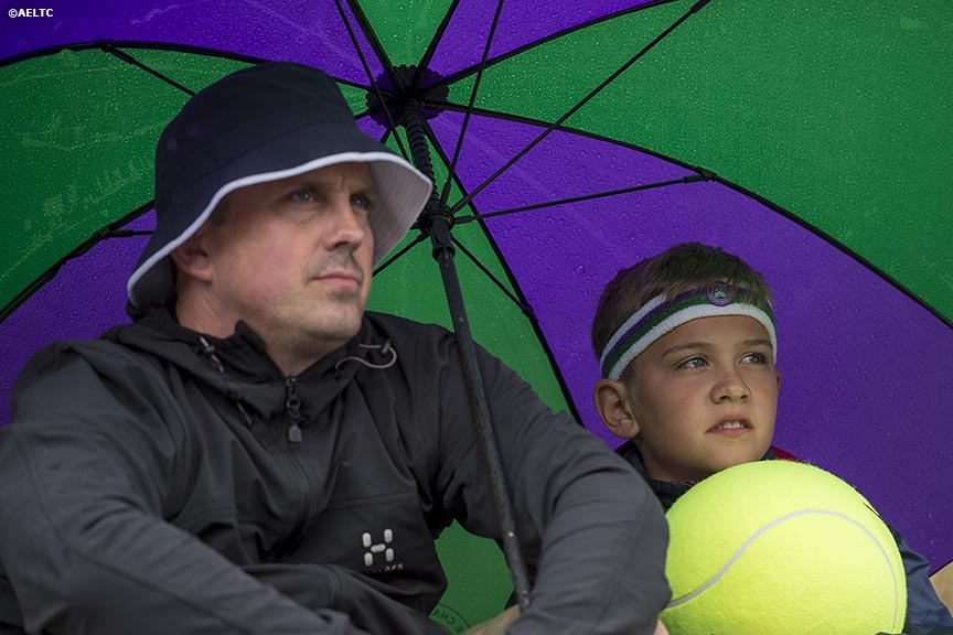"""Fans sit under an umbrella as they watch a match on Henman Hill at the All England Lawn and Tennis Club in London, England Saturday, June 28, 2014 during the 2014 Championships Wimbledon."""